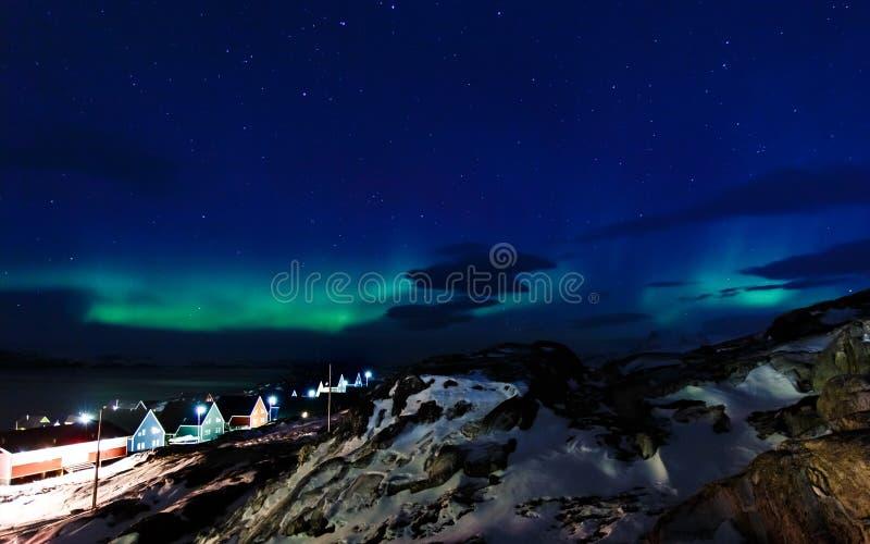 Noordelijke lichten over het Inuit-dorp, de fjord en de bergen, nabijgelegen Nuuk-stad, Groenland stock afbeelding