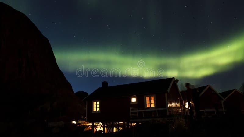 Noordelijke lichten over hutten in Hamnoy stock fotografie