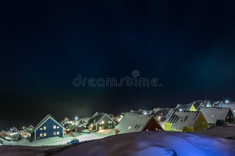 Noordpool polaire nacht over kleurrijke inuithuizen in een voorstad van boog stock foto