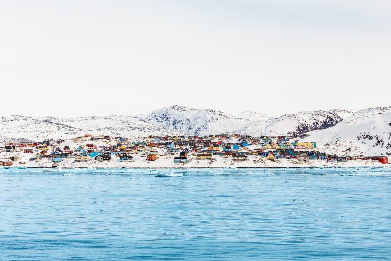 Noordpoolstadspanorama met kleurrijke Inuit-huizen op rotsachtige hil stock foto's