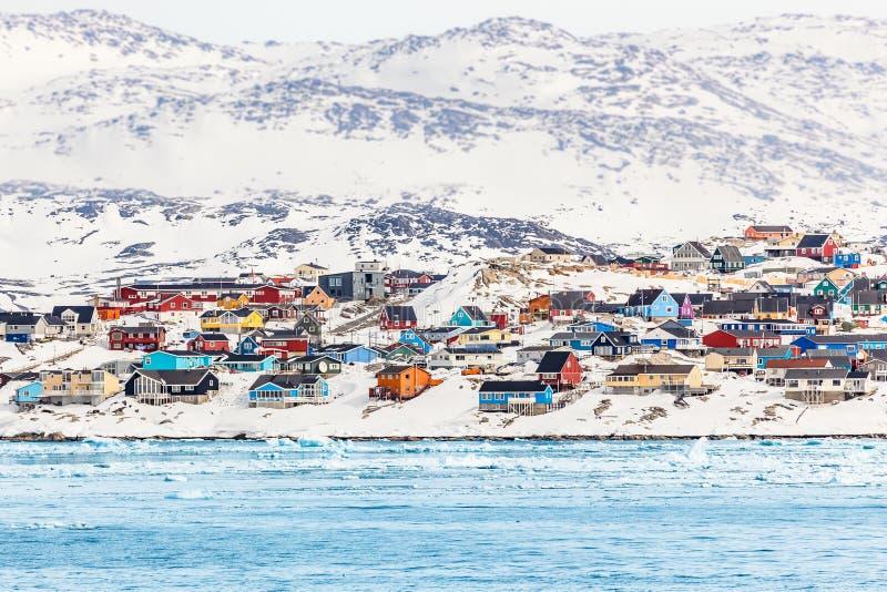 Noordpoolstadspanorama met kleurrijke Inuit-huizen op rotsachtige hil stock afbeelding