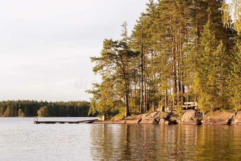 Noords meerlandschap van een houten dok bij een rotsachtige kust met pijnboombomen stock afbeeldingen