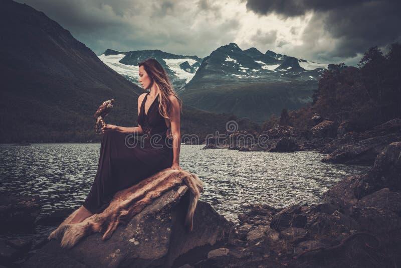Noordse godin in ritueel kledingstuk met havik dichtbij wild bergmeer in Innerdalen-vallei royalty-vrije stock foto's