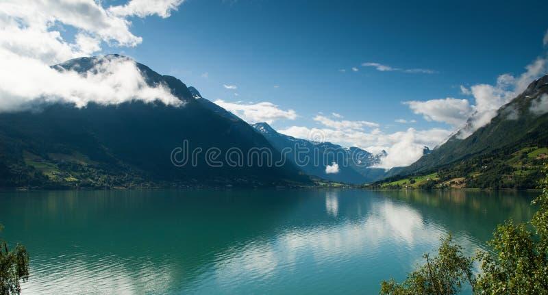 Noors bergmeer met het overweldigen van wolken stock fotografie