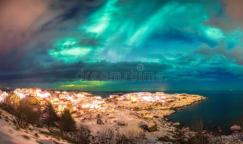 Noors dorp die op noordpoolkustlijn met noordelijke ligh gloeien stock afbeeldingen