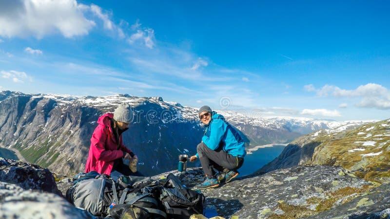Noorwegen - een paar die ontbijt in de lange bergen met een mening over een meer hebben stock foto