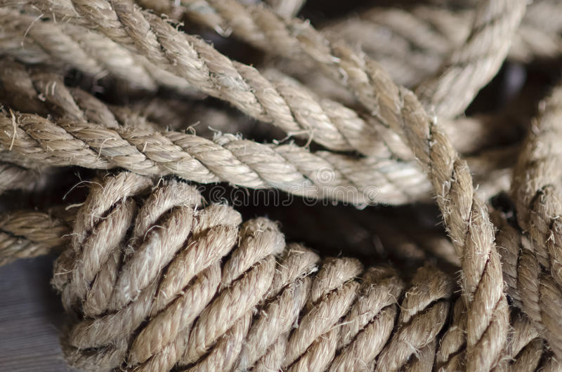 Noose Rope for a Hanging. Old natural hemp rope tied in a noose coiled on the ground closeup Shallow depth of field stock photography