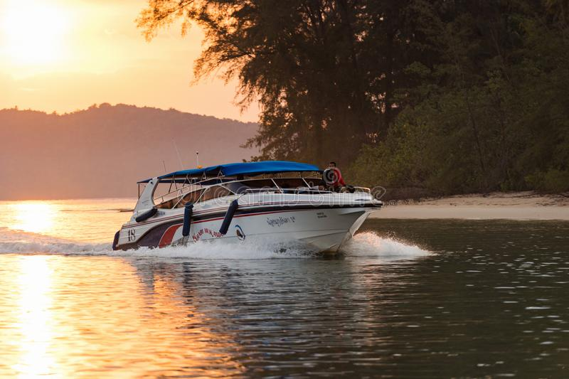 Modern speedboat floats in the water at the orange sunset royalty free stock photos