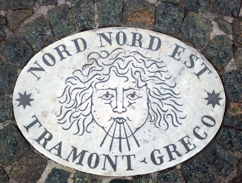 Nord Nord Est norr norr öst - ett huvud som symboliserar riktningen av vinden En forntida bild på en marmortjock skiva i St Peter arkivfoto