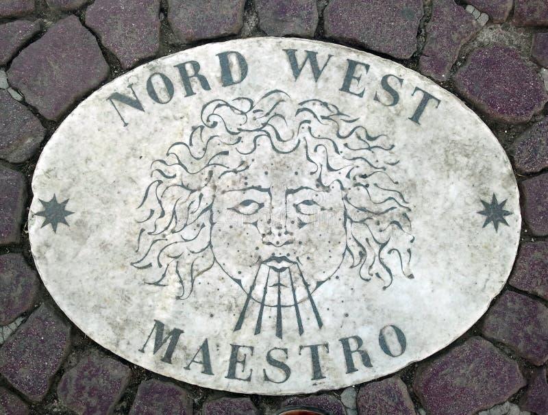 Nord västra nordvästligt - ett huvud som symboliserar riktningen av vinden En forntida bild på en marmortjock skiva i fyrkant för royaltyfria bilder