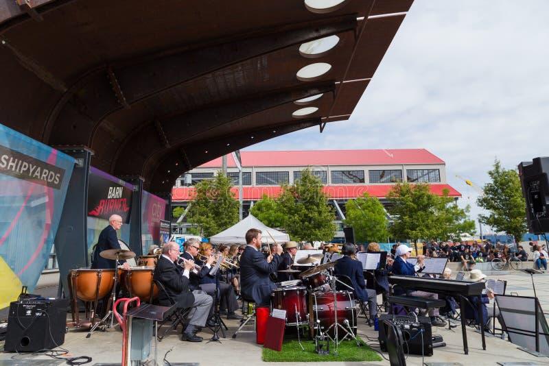 NORD-VANCOUVER BC KANADA - 9. JUNI 2019: Ein Jazzbandensemble, das Holzblasinstrument und Messinginstrumente mit einem Leiter spi lizenzfreie stockfotografie