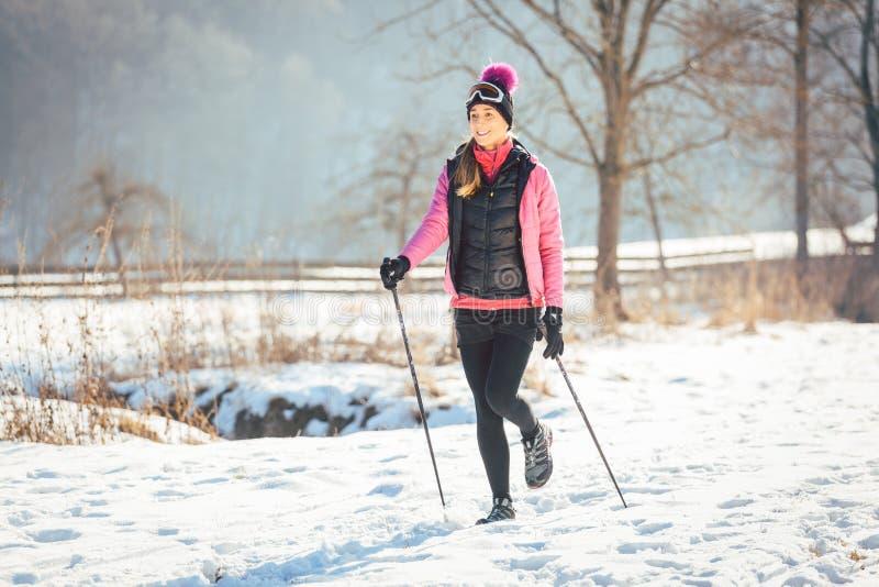 Nordic apto de la mujer que camina en paisaje del invierno imagen de archivo