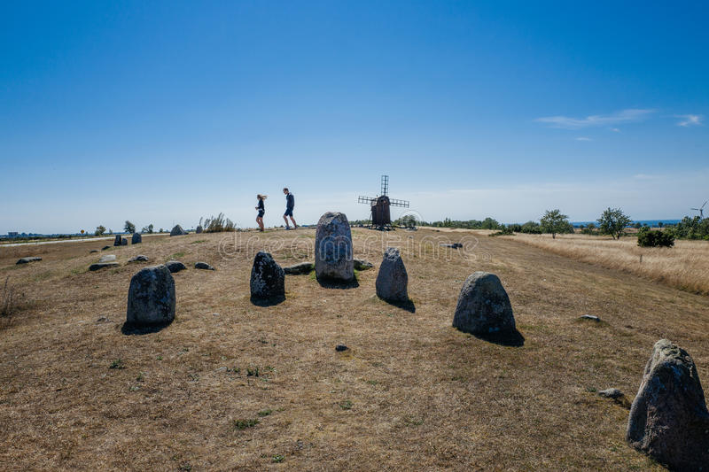 Nordic bronze age grave field in Sweden. Gettlinge, Sweden - August 15, 2015: Tourists explore Gettlinge grave field with its famous stone ship. The oldest stock photos