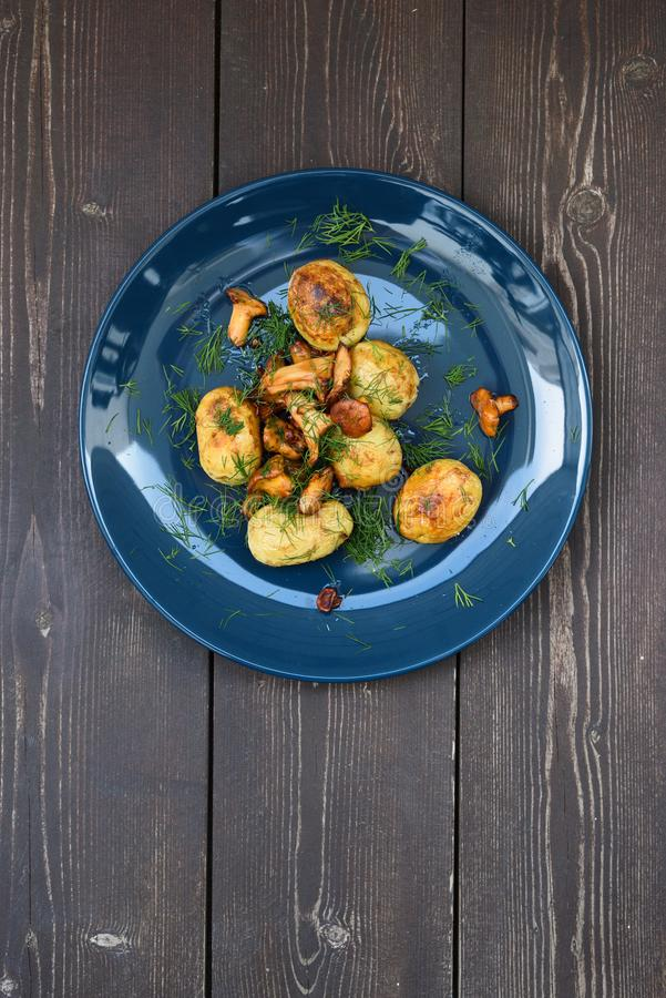 Nordic cuisine. Healthy vegetarian meal. Fried forest mushrooms, potatoes and dill on navy blue plate on rustic dark background c stock photo
