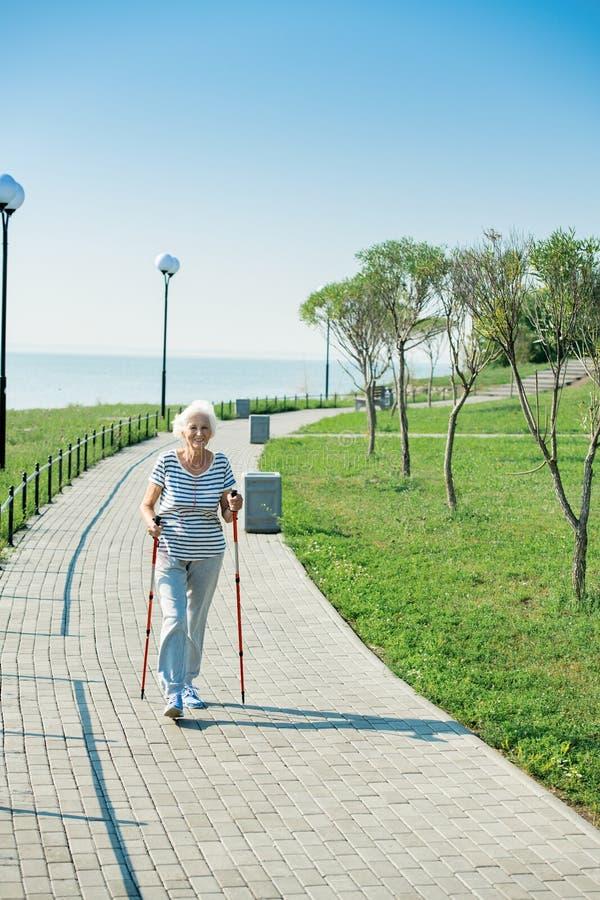 Nordic supérieur actif de femme marchant en parc photo libre de droits