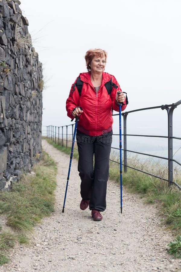 Nordic superior da mulher que anda na fuga rochosa fotografia de stock
