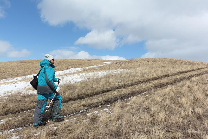 Nordic Walking - adult woman climbing on a mountain. Bald, Bugotaksky hills, Novosibirsk region, Russia stock photo