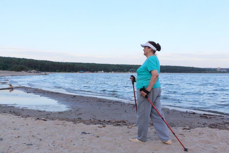Nordic Walking - elderly woman is hiking along the river. Nordic Walking - elderly woman in a green T-shirt is hiking along the river on a summer evening stock photography