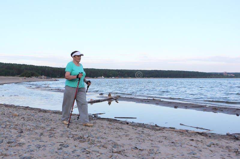 Nordic Walking - elderly woman is hiking along the river. Nordic Walking - elderly woman in a green T-shirt is hiking along the river on a summer evening royalty free stock image