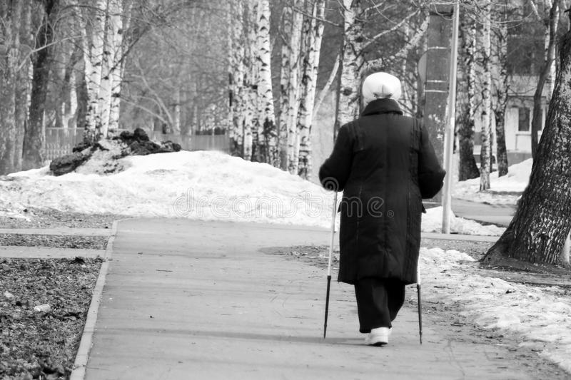 Nordic Walking - elderly woman is hiking, elderly woman in the Park. Outdoors royalty free stock photos