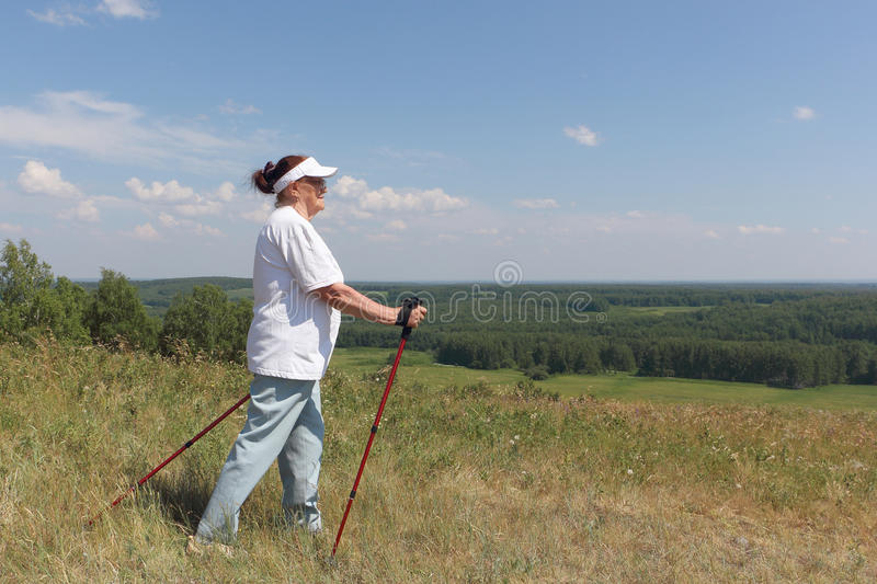 Nordic Walking - elderly woman is hiking. In the summer royalty free stock photos