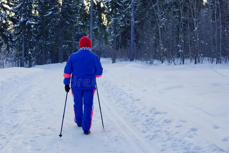 Nordic walking.an elderly woman leads a healthy lifestyle. Winter Park snow forest royalty free stock photography
