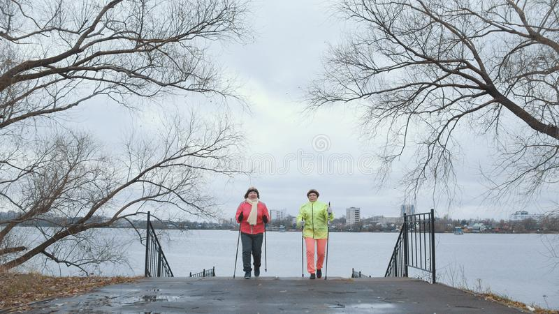 Nordic walking for elderly women outdoor - two senior ladies have training outdoor. Wide angle stock photography