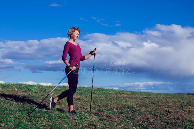 Nordic walking, exercise, adventure, hiking concept -a woman hiking in the nature. Nordic walking, exercise, sport, adventure, hiking concept -a woman hiking in stock images