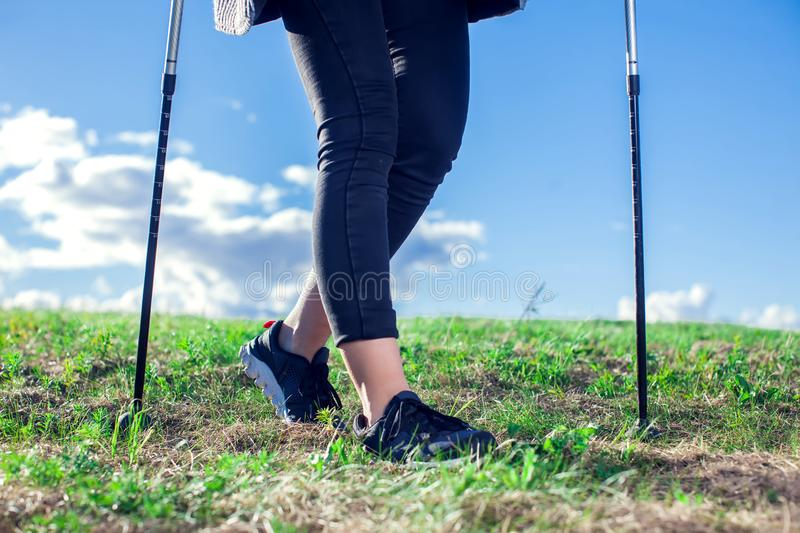 Nordic walking, exercise, adventure, hiking concept -a woman hiking in the nature. Nordic walking, exercise, sport, adventure, hiking concept -a woman hiking in royalty free stock image