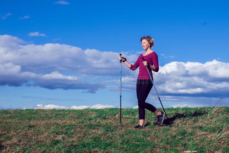 Nordic walking, exercise, adventure, hiking concept -a woman hiking in the nature. Nordic walking, exercise, sport, adventure, hiking concept -a woman hiking in stock photos