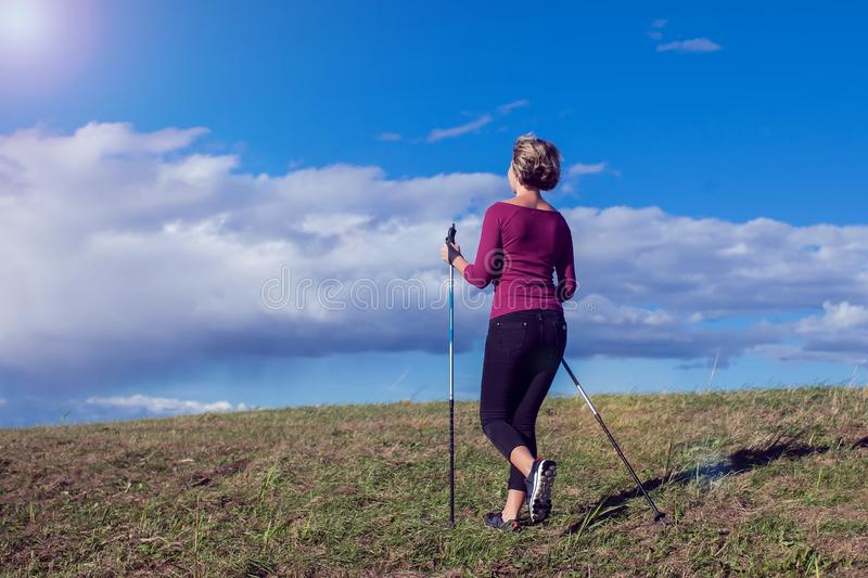 Nordic walking, exercise, adventure, hiking concept -a woman hiking in the nature. Nordic walking, exercise, sport, adventure, hiking concept -a woman hiking in stock photo