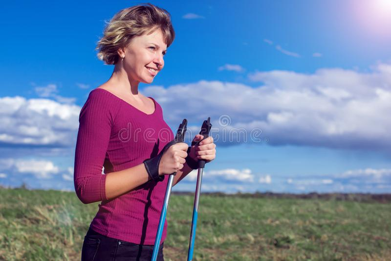 Nordic walking, exercise, adventure, hiking concept -a woman hiking in the nature. Nordic walking, exercise, sport, adventure, hiking concept -a woman hiking in royalty free stock photography