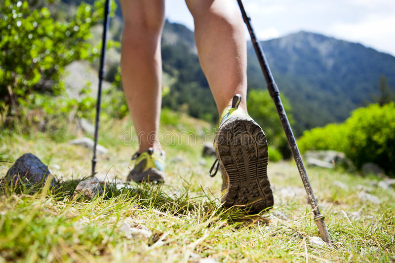 Nordic walking legs in mountains. Woman hiking in mountains, adventure and exercising stock photos