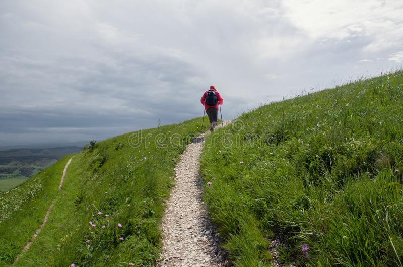 Nordic walking. Man with sticks for Nordic walking is on  path in the mountains. Outdoor stock images