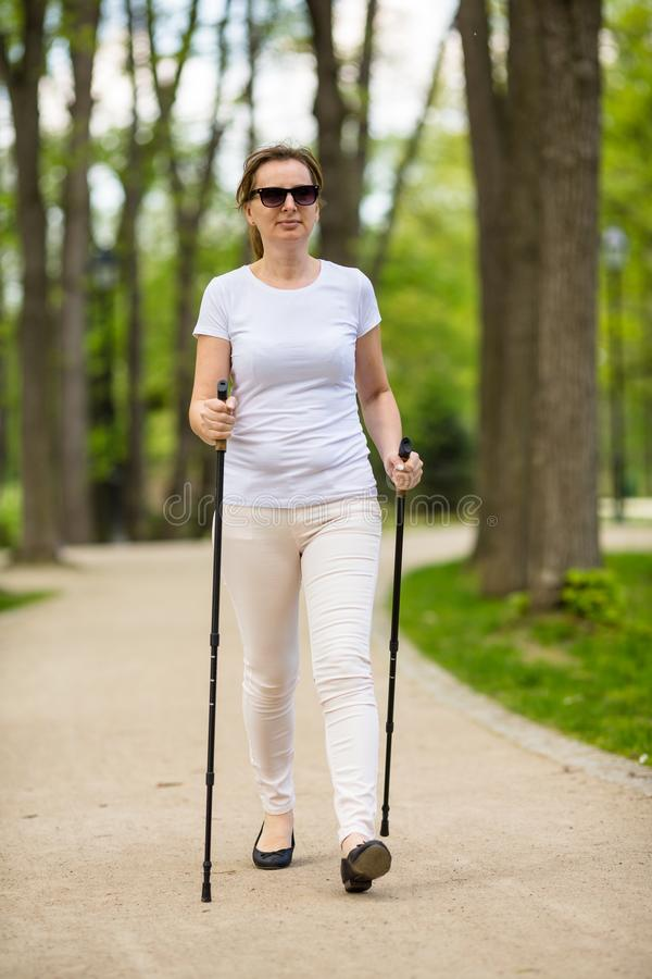 Nordic walking - middle-age woman working out. In city park royalty free stock photography