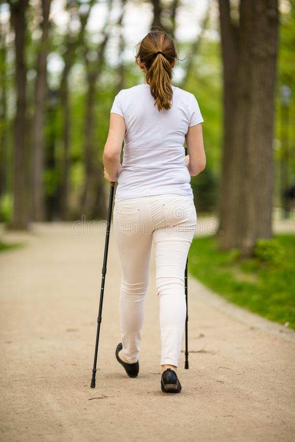 Nordic walking - middle-age woman working out. In city park stock image