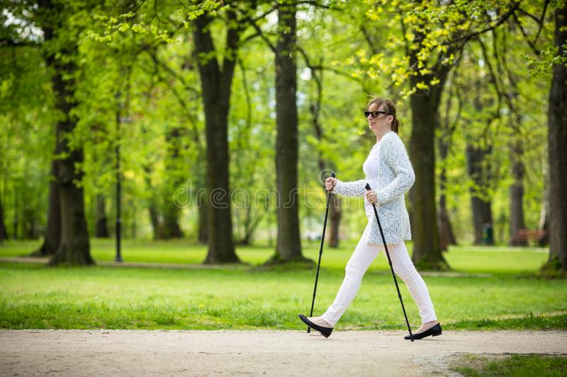Nordic walking - middle-age woman working out. In city park stock photos