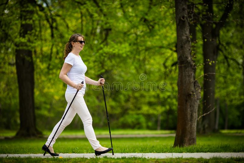 Nordic walking - middle-aged woman working out. In city park royalty free stock photography
