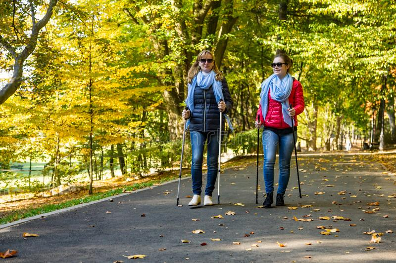 Nordic walking - people working out in park. Nordic walking - active people working out in park stock images