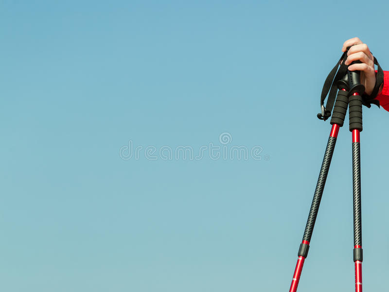 Nordic walking. Red sticks on blue sky background. Nordic walking equipment. Closeup of red sticks on blue sky background with copy space. Active and healthy stock photography