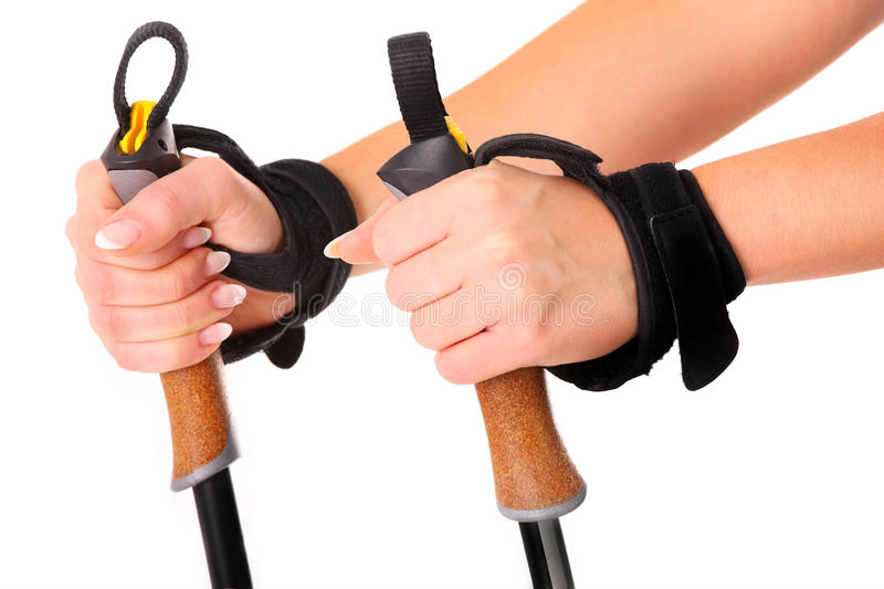 Nordic walking sticks. A close-up of female hands holding nordic walking sticks over white background stock images