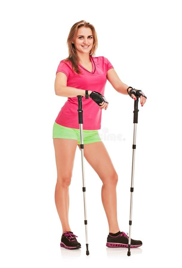 Nordic walking woman. Nordic walking athletic woman posing on white background royalty free stock photo