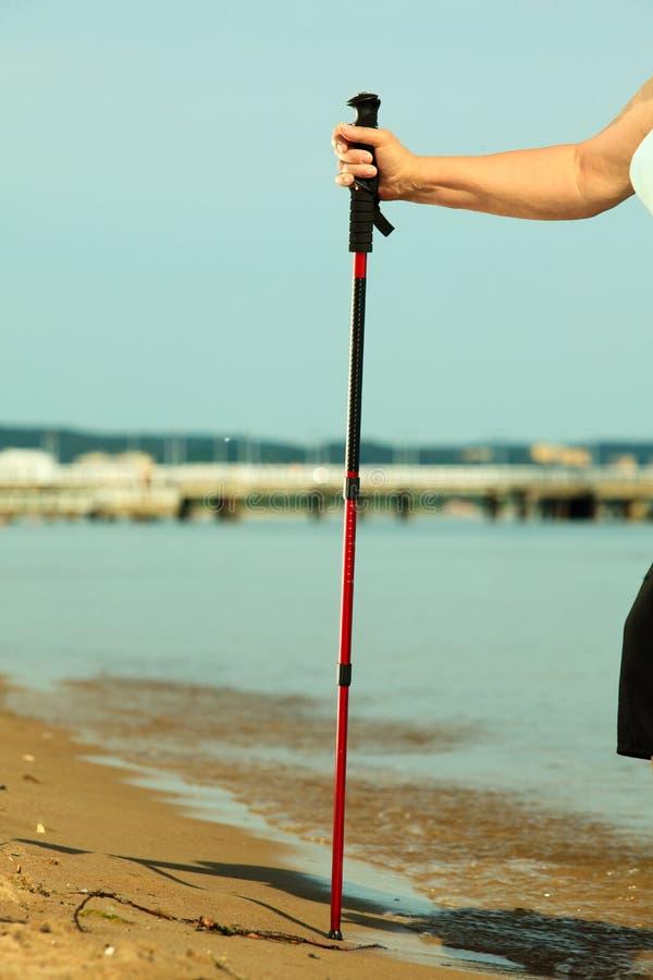 Nordischer Spazierstock in der weiblichen Hand auf einem sandigen Strand stockfotografie