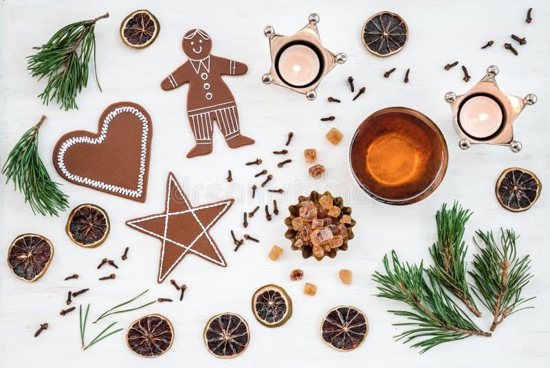 Nordischer Weihnachtsdekor mit Kerzen-, Tee- und Ingwerkeksen stockfotos