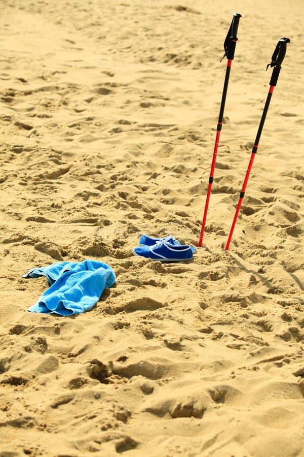 Nordisches Gehen Stöcke und violette Schuhe auf einem sandigen Strand stockbild
