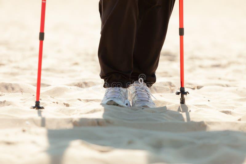Nordisches Gehen Weibliche Beine, die auf dem Strand wandern lizenzfreie stockfotos