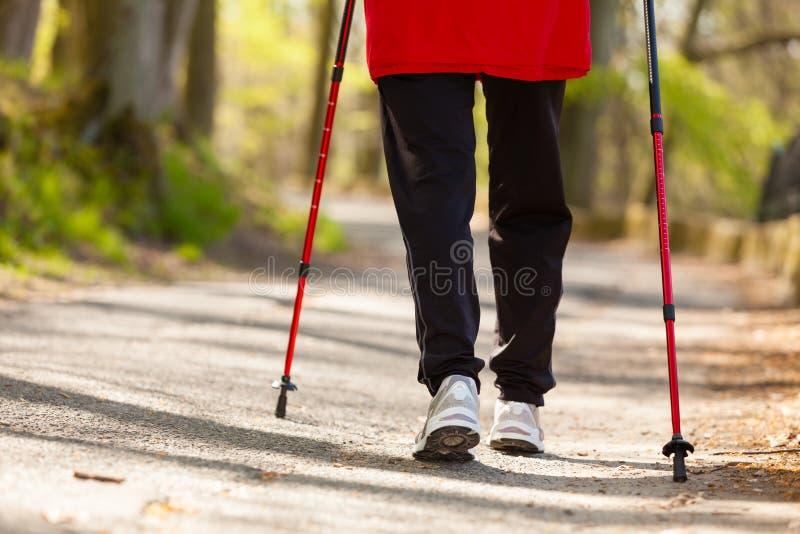 Nordisches Gehen Weibliche Beine, die im Park wandern lizenzfreie stockbilder