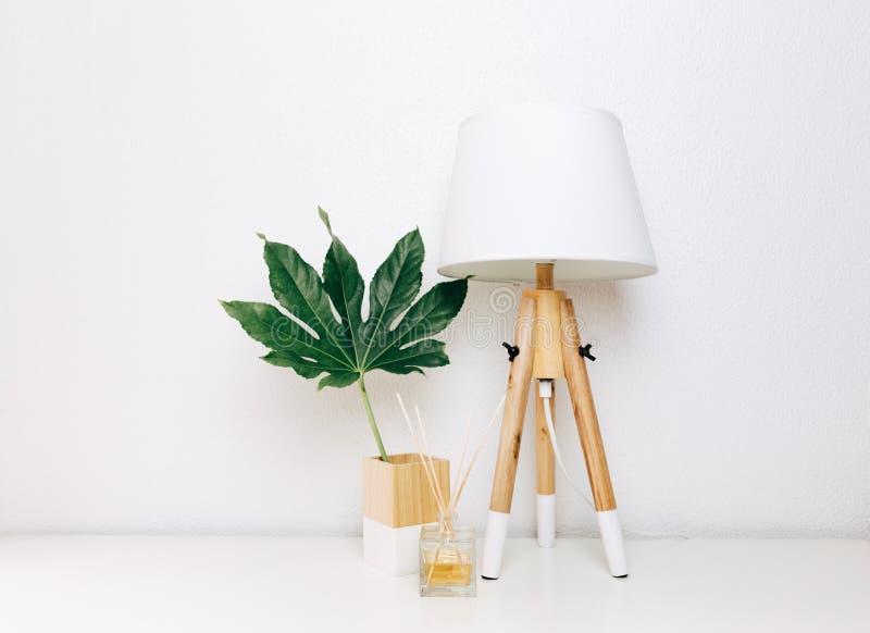 Nordisk modern vardagsrum med tabelllampan, hem- doft och det tropiska bladet arkivbild