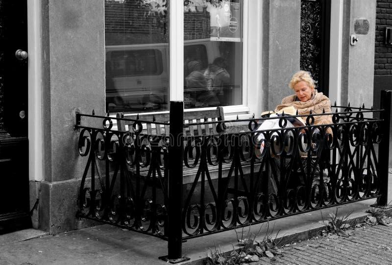 Nordisk utomhus- livsstil, härlig äldre blond kvinna som läser en bok på en balkong, Amsterdam