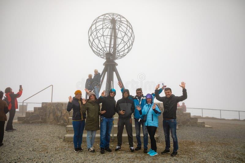Nordkapp, Норвегия - 26 06 2018: Группа в составе туристы держит прийти к известным северным накидке и любов принять фото с стоковая фотография rf
